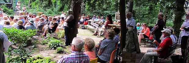 Fast 100 Gäste sitzen bei schönstem Wetter vor dem Sommerhaus.